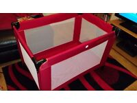 Red travel cot by Kiddicare