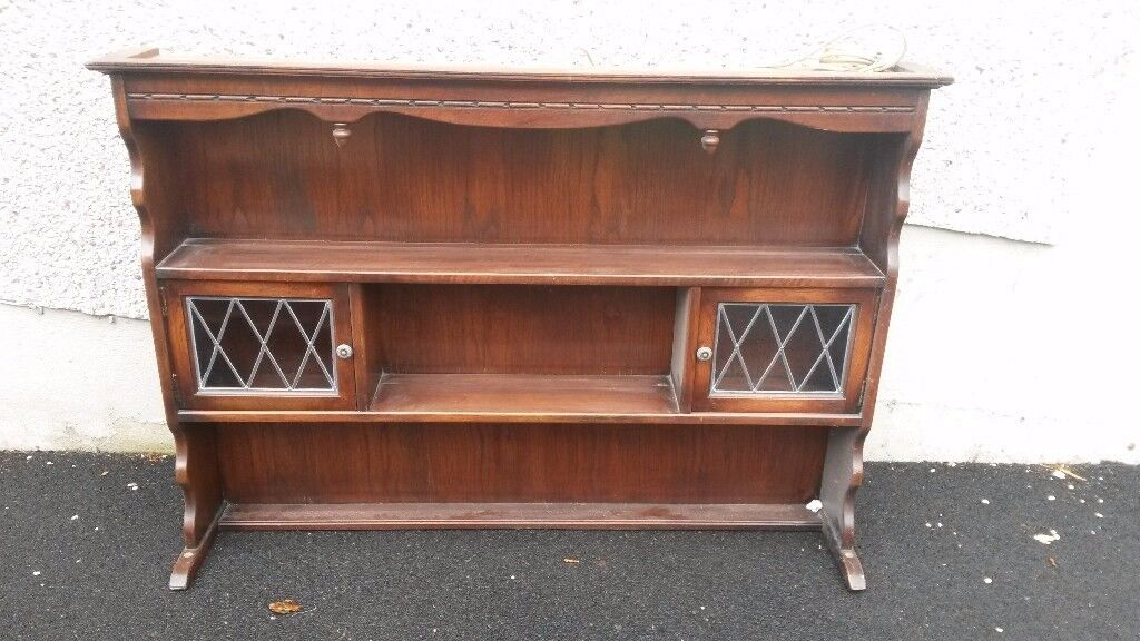 Oak shelving unit with leaded glass cupboards and light