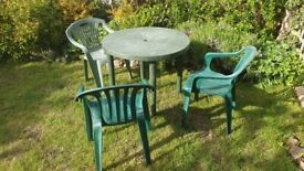 Green plastic garden chairs and table