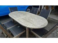 Large extending oval teak table and chairs