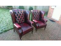 A pair of ox blood red leather Chesterfield wing chairs