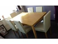 6 x 4 foot wide Oak table and 6 high back cream leather chairs.