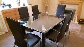 5ft Glass Dinjng Table and Six Faux Leather Chairs. Table and Chairs have Chrome Deatail
