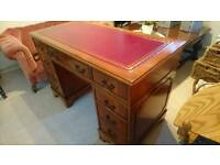 An ox blood red leather top traditional double pedestal desk