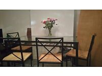 Black metal frame and glass table with four chairs