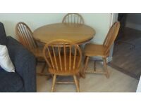 Wooden, round dining room table and 4 wooden chairs