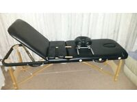 Black massage couch with adjustable panel for siting on couch or lying down