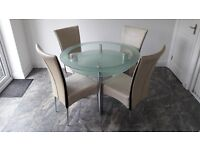 Glass dining table with chrome legs and four matching cream leather chairs