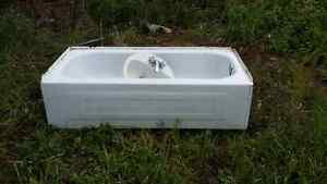 Free white metal bathtub and sink with taps.
