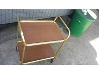 gold coloured framed tea trolley with light brown wood shelves