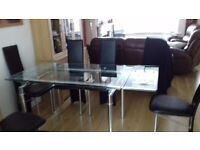Extending glass and chrome dining table and six chairs