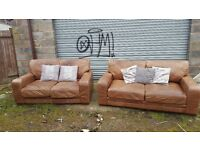 Comfy Brown tan leather sofa suite. 3 and 2 seaters, used with a bit of wear.can deliver