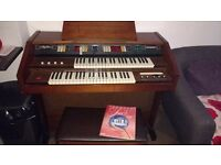 Howard Skyline Electric Organ With Seat with lifting lid containing piano books