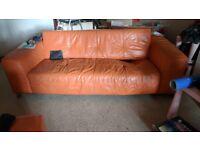 2 orange 3 seat leather sofas