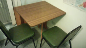 foldable wooden table with two leather/metal chairs