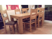 Solid Oak dining room table with six matching chairs.