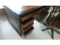An Antique brown mahogany desk and leather Chesterfield captains chair