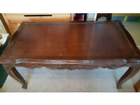 Solid wood coffee table with glass top.