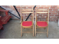 2 wood framed folding chairs with red seats