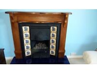 Cast iron fireplace with medium oak and tile surround, with tiled hearth.