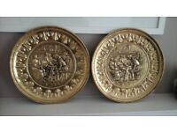 A pair of old matching pressed metal wall hanging decorative plaques