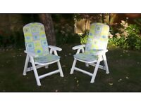 Four white plastic garden chairs and seat pads for sale