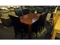 Dark solid wood dining table with 6 leather chairs