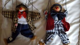 Two wooden clown marionette string puppets .