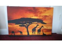 Giraffe family and tree silhouetted under orange sunset printed on canvas