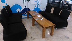 Large black chairs with solid wood coffee tables