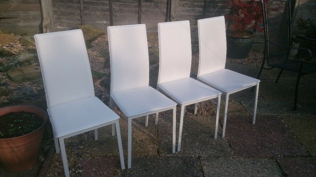 Four white dining chairs