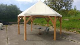 Pavilion Marquee gazebo. Hexagonal timber framed structure with canvas roof and sides.