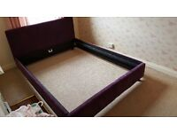 King size purple material bed frame.