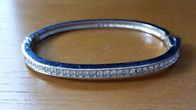 Boxed Swarovski silver coloured metal and crystal bangle with clip fastening