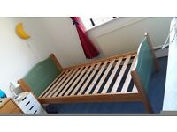 A solid wooden single bed.