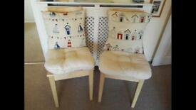 Two Ikea Bertil dining chairs with cushions