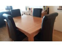 Solid oak dinning table with 6 black faux leather chairs.