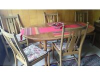 Solid wood dinning table with six chairs and cushions.