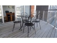 Patio table, granite top, diameter 41 inches. Excellent condition. Four metal chairs.
