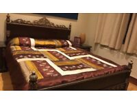beautifully carved wooden king size bed and two side tables
