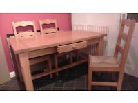 Solid wood dining table with drawer and 4 chairs.