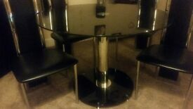 Black Glass/Chrome Round Dinning table with 4 Matching High back Black Vynil/Chrome Frames