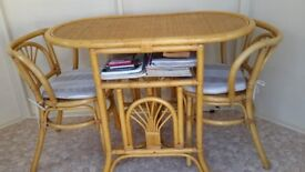 A neat cane table and two chairs