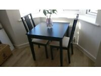 Black wooden dining table with 4 matching upholstered chairs
