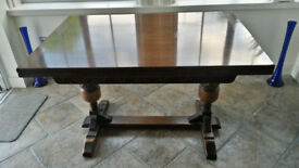 Solid dark oak dining table with twin-leaf extension.