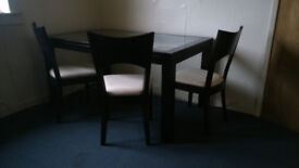 Glass topped dining table with four chairs.