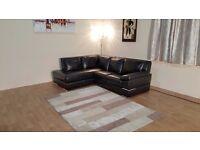 Ex-display Primo black leather corner sofa with chrome feet