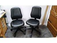 A pair of Ikea black leather desk chairs