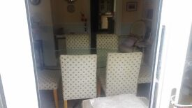 oval glass table with chrome legs and six beige chairs,