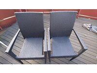 Two black rattan garden chairs